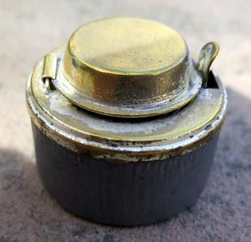 BRASS INKWELL WITH SPRING LOADED LID AND INTERNAL GLASS BOTTLE.