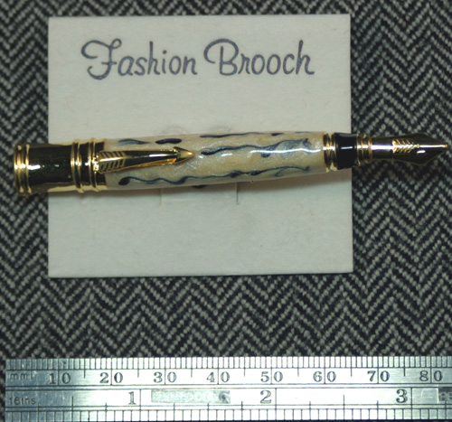 A PEN PIN PATTERNED AFTER A DUOFOLD.